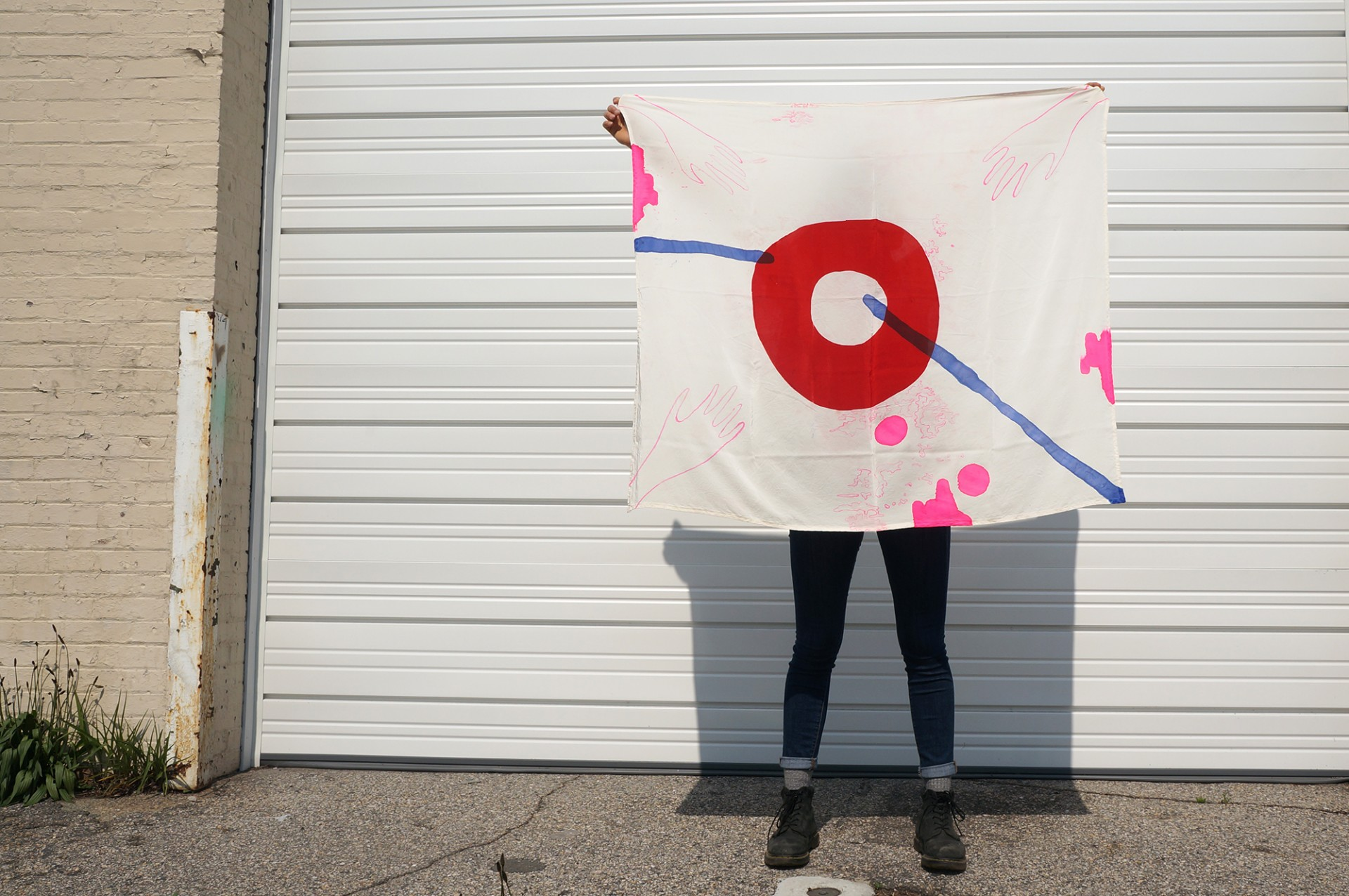Model holding scarf against wall. Scarf design include bold red circle, pink squiggles and blue lines.