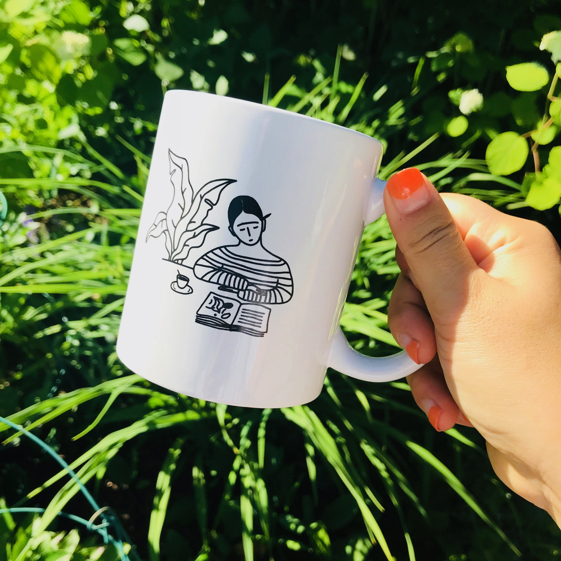 Hand holding white ceramic mug. Simple black drawing on mug features girl in striped shirt reading at table with plant to her left.