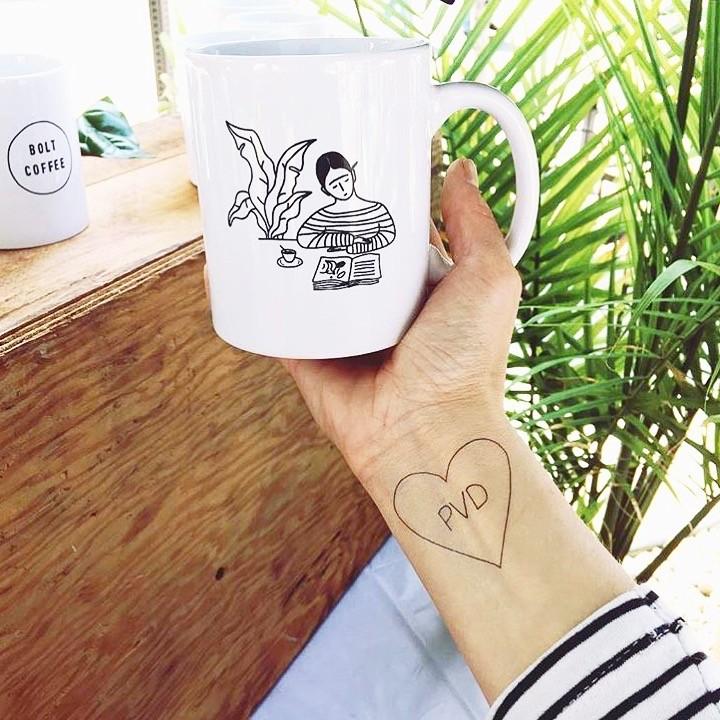 "Hand holding white ceramic mug. Simple black drawing on mug features girl in striped shirt reading at table with plant to her left. Hand holding mug has a tattoo of a heart with the text ""PVD"" inside."