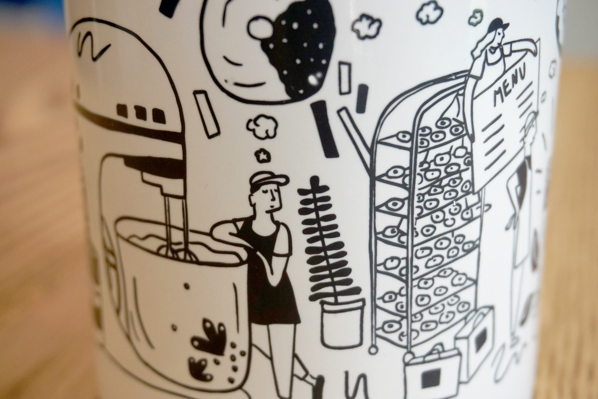 Detail of mug that shows baker leaning against oversized mixer dreaming of donuts.
