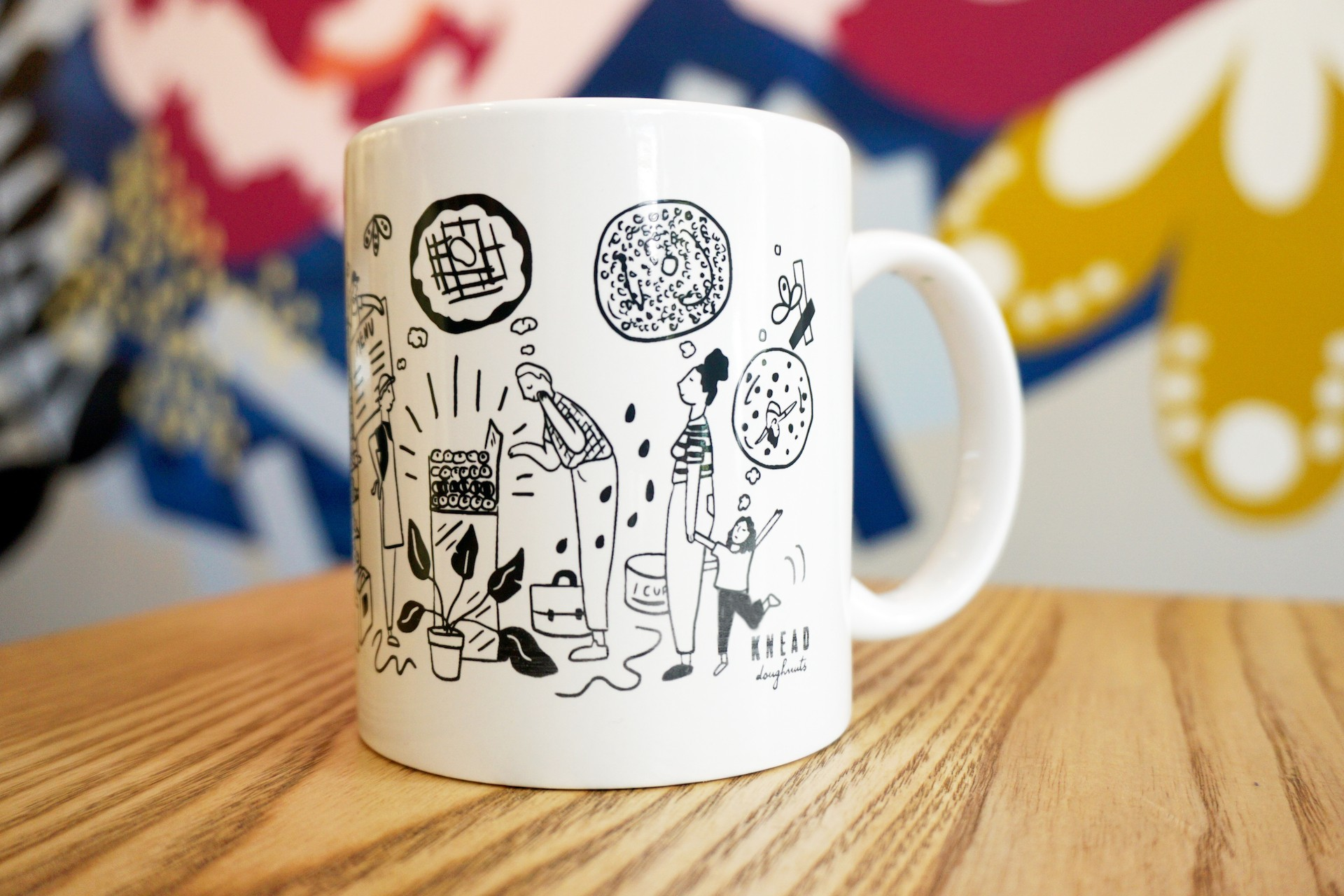 White ceramic mug on wooden table with colorful mural in background. Mug illustration includes oversized kitchen items, donuts, bakers and Knead customers..