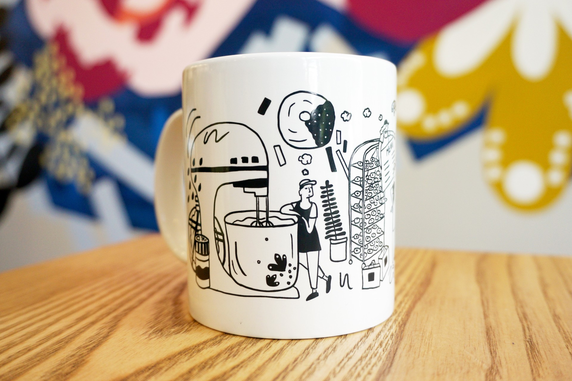 White ceramic mug on wooden table with colorful mural in background. Mug illustration includes oversized kitchen items and bakers.