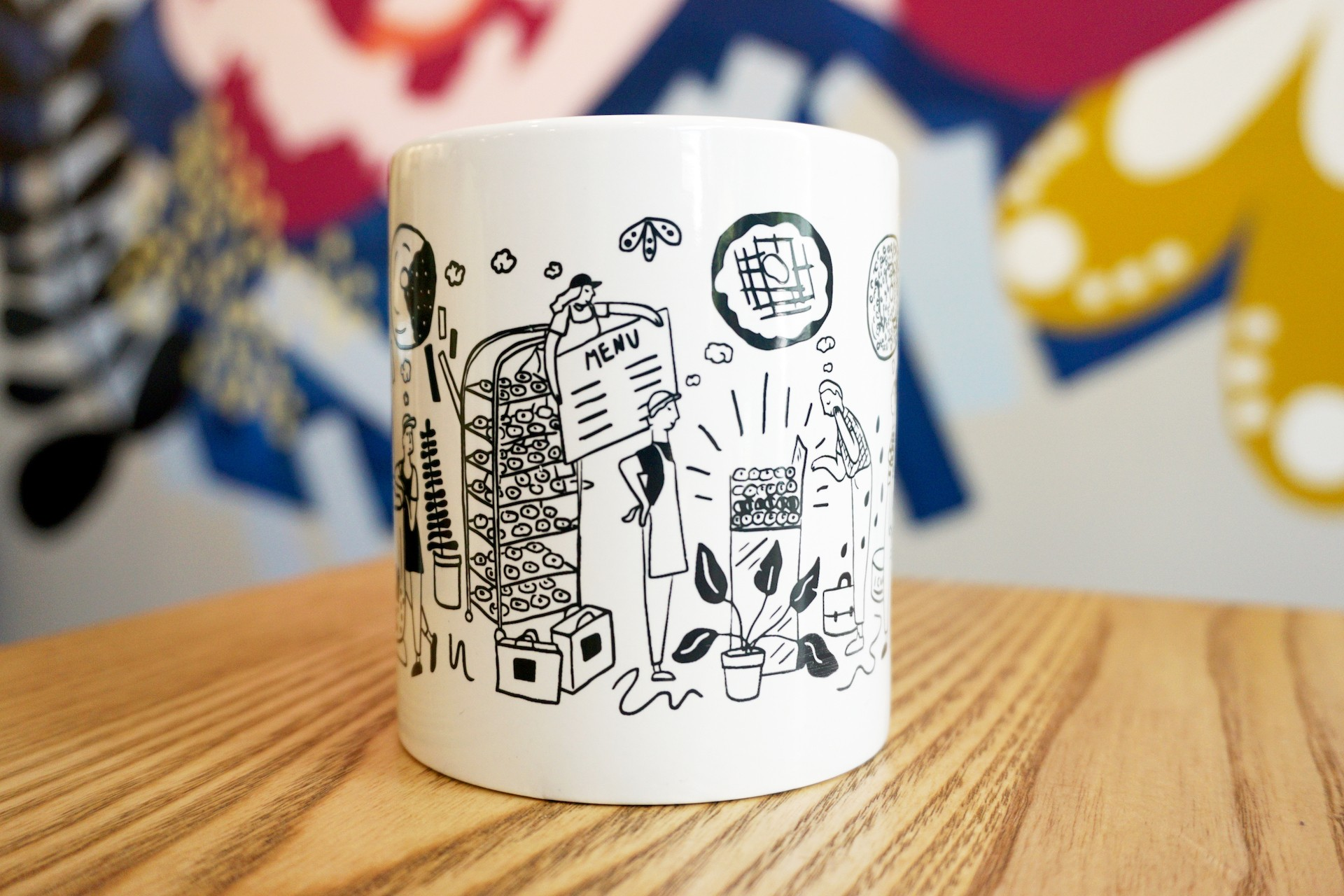 White ceramic mug on wooden table with colorful mural in background. Mug illustration includes oversized kitchen items, donuts and bakers.