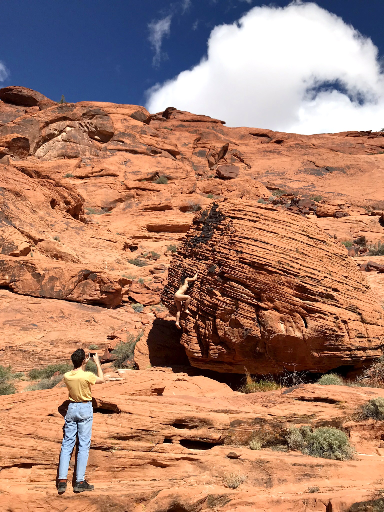 Photograph of Nevada canyons. 3/4 of image are bright red rocks. Figure in bottom left corner has back towards viewer and is taking picture of nude woman climbing boulder in right side of photograph. Sky is blue with clouds.