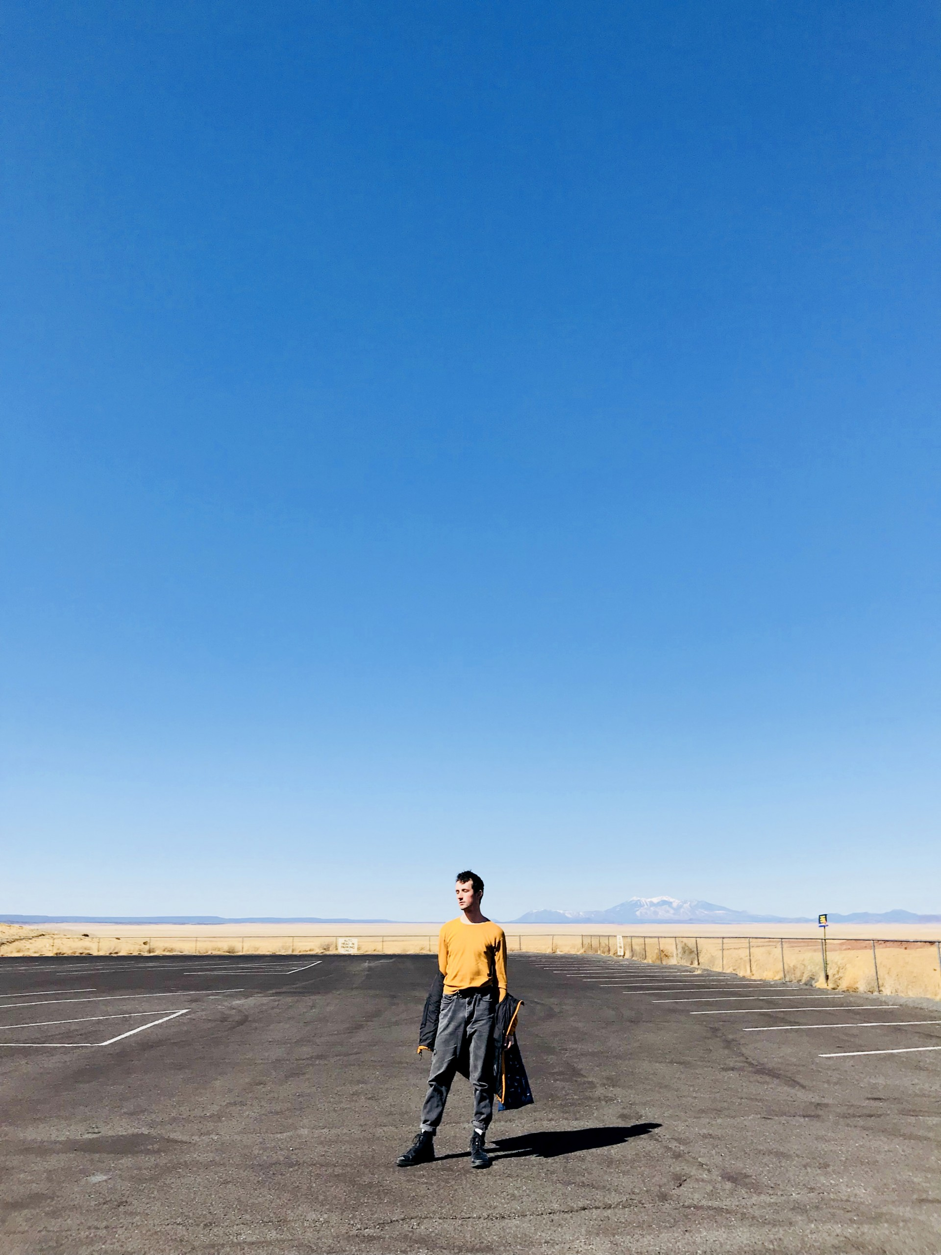 Male model standing in empty parking lot. 3/4 photograph is blue sky. Model has jacket half hanging off arms.