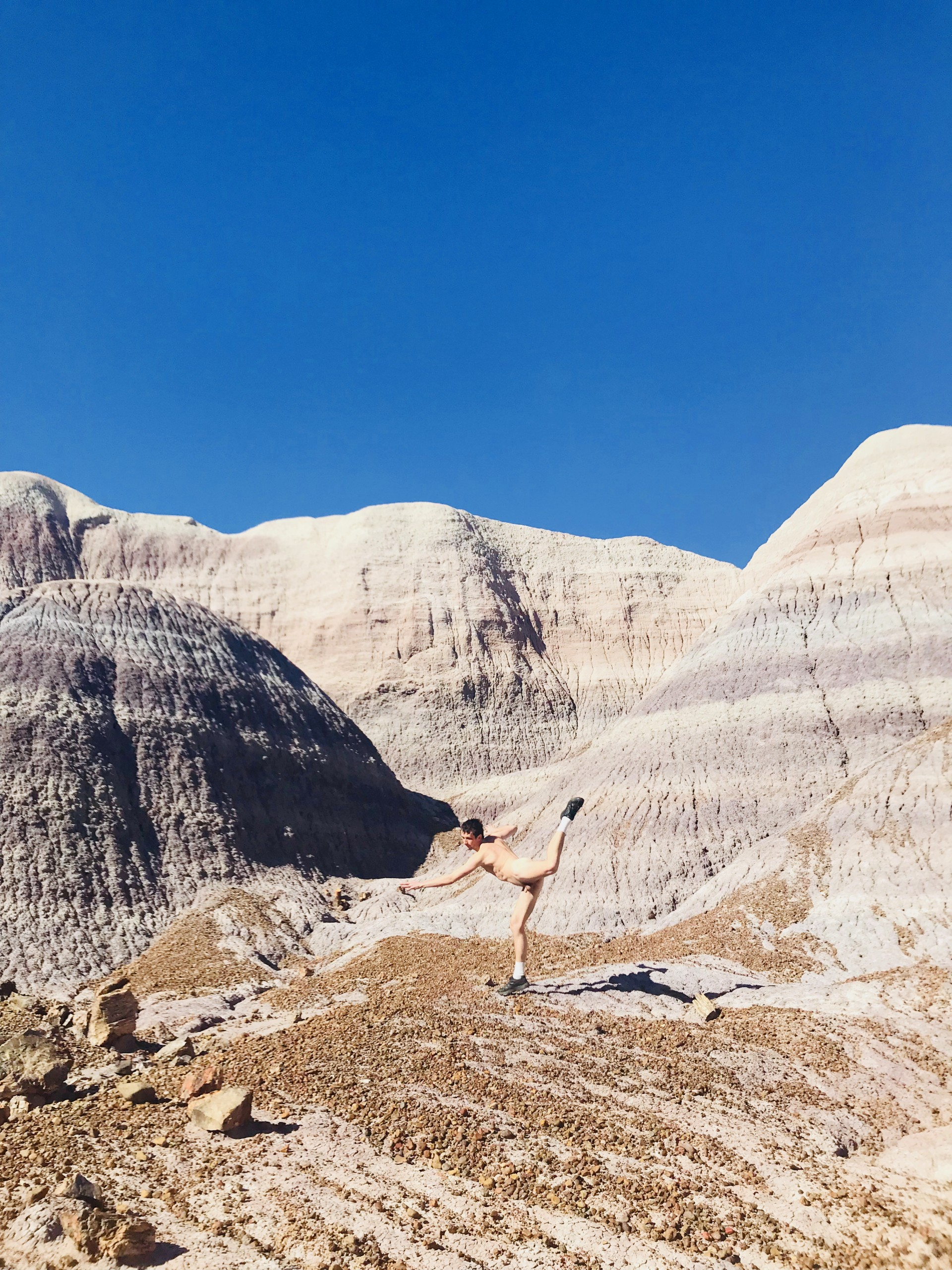 Photograph of Blue Mesa in Petrified Forrest in Arizona. Nude male model in center of image mid leap with leg in air.
