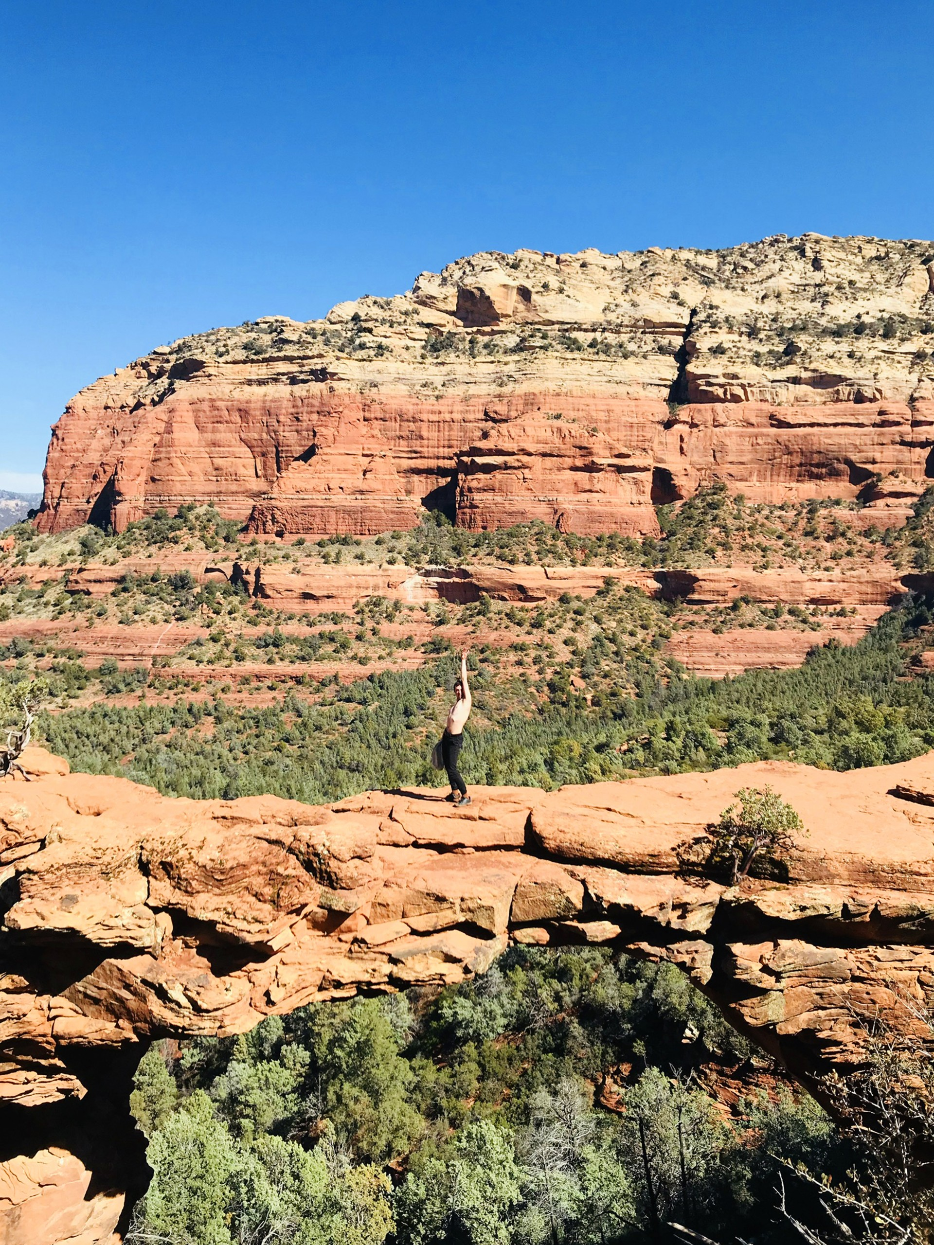 Photograph of Devil's Bridge in Sedona Arizona. Male model stands in center of bridge topless with hand draped above head.