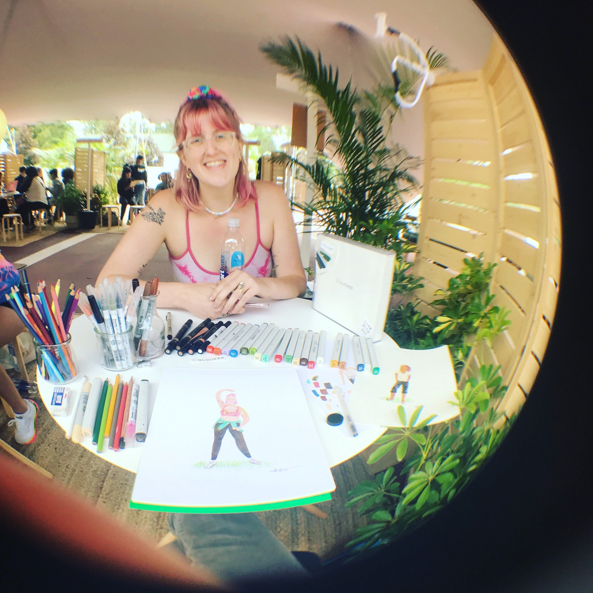 Fisheye angle photograph of portrait drawing station with markers, paper and model