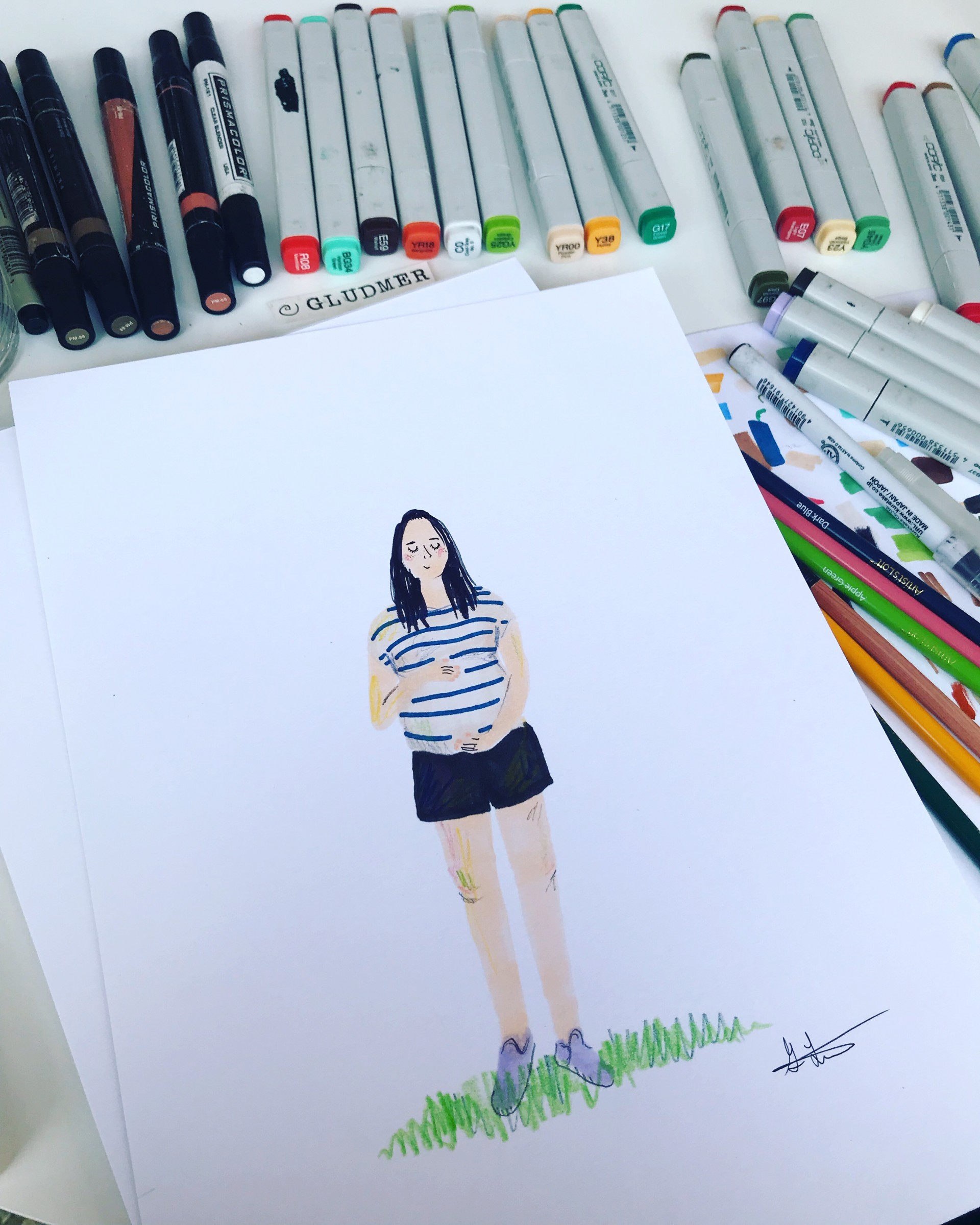 Markers surrounding portrait of pregnant woman wearing striped shirt and black shorts.