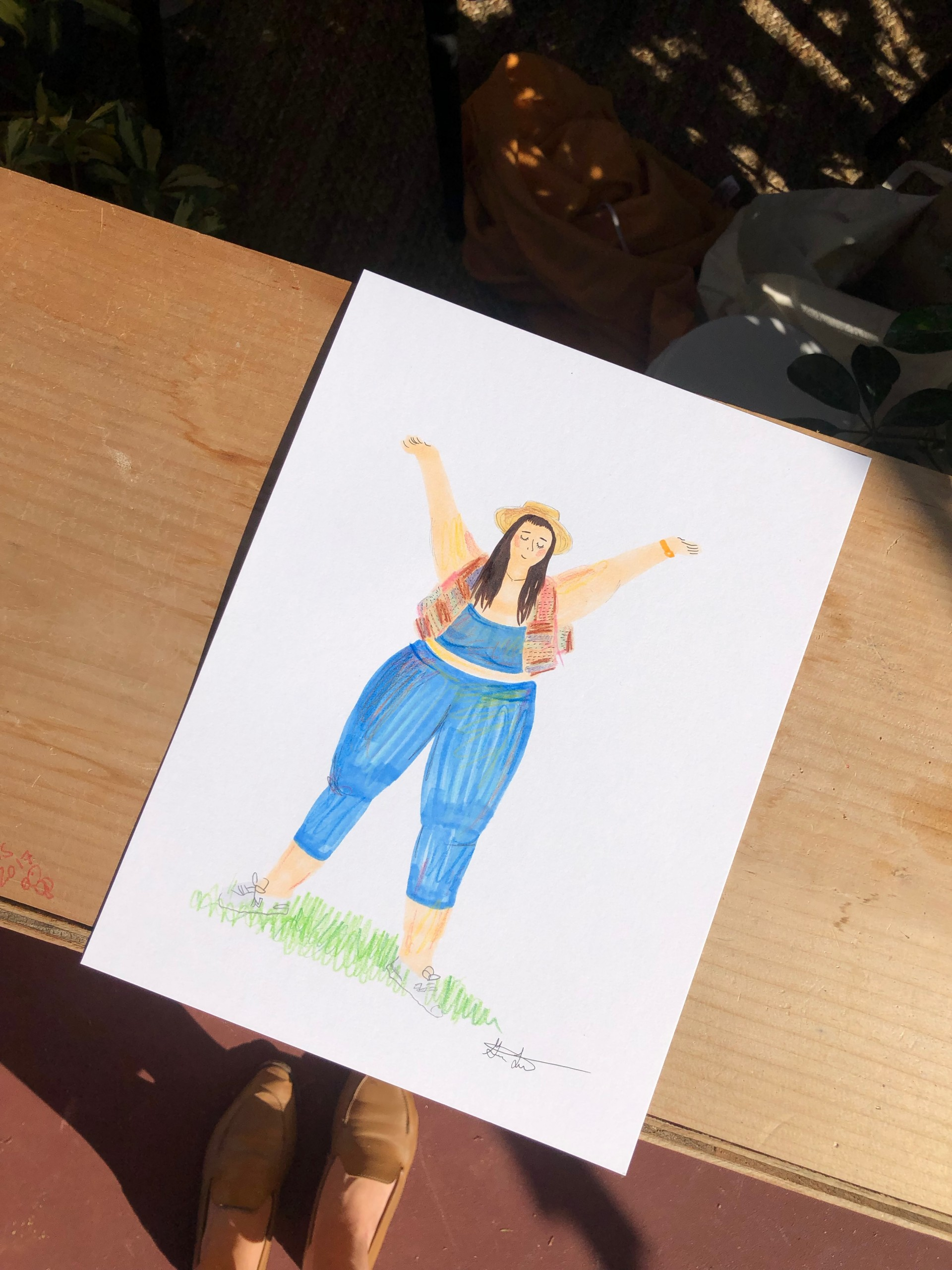 Drawing of girl in blue leggings and blue sports bra with hands above head.