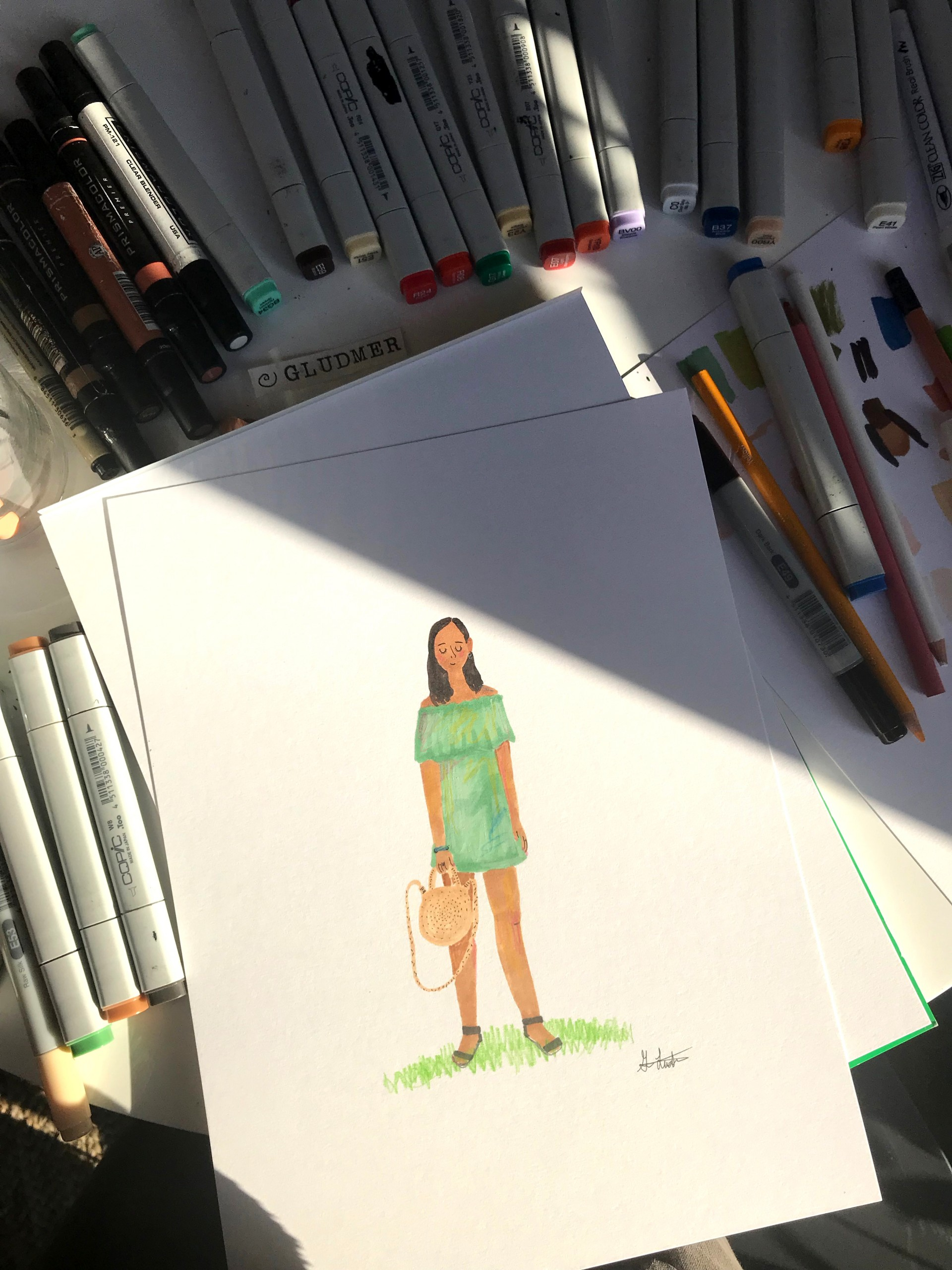 Markers surrounding drawing of girl wearing strapless light green dress holding wicker bag.
