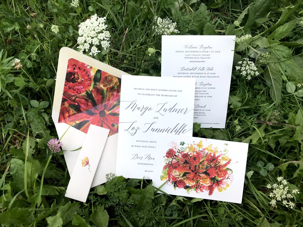 Wedding invitation suite with floral illustrations in bed of wildflowers