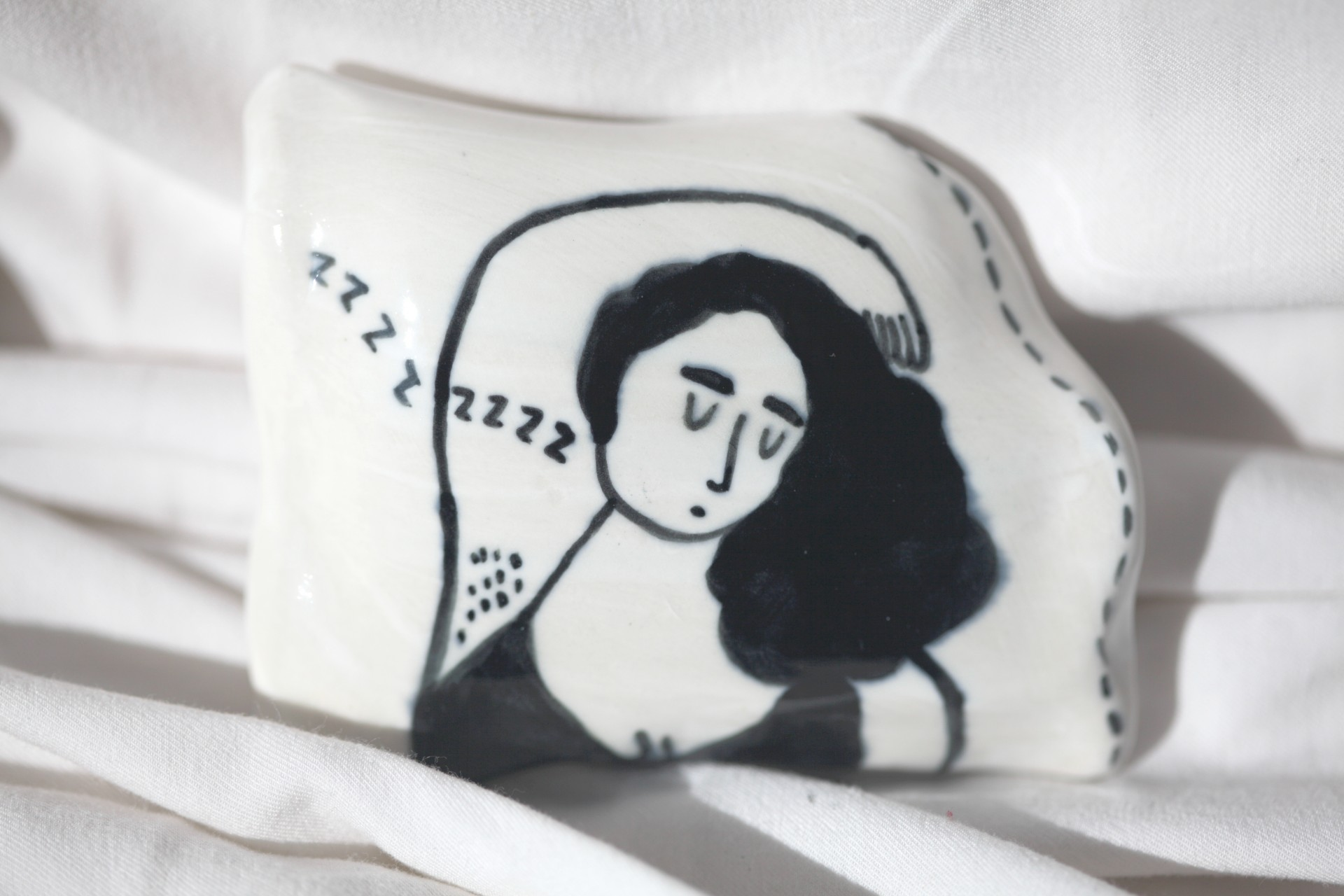 One porcelain pillow painted with a girl sleeping on it photographed against white sheets.